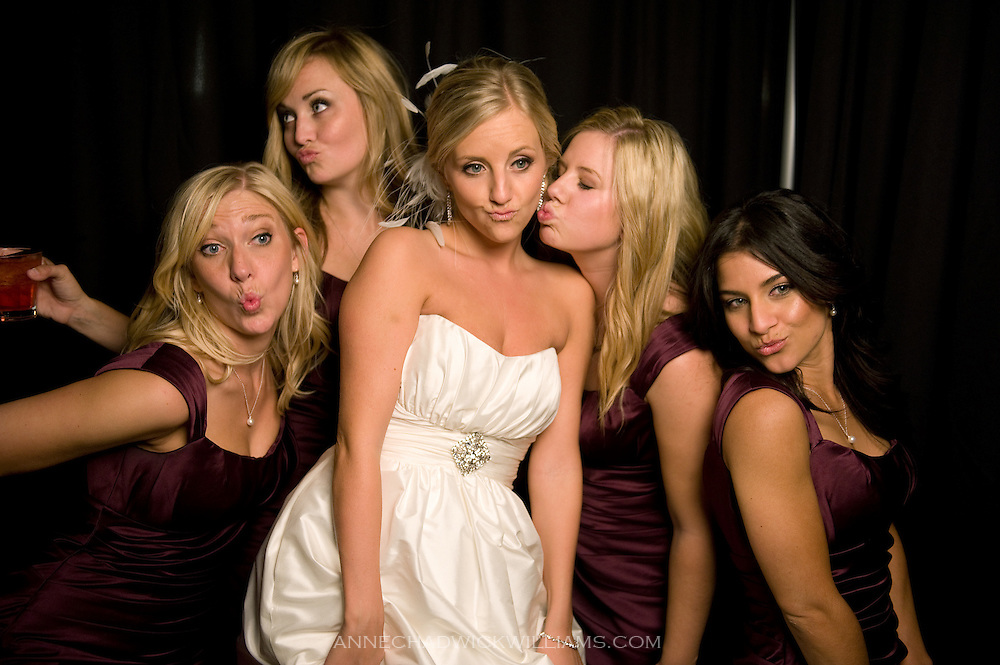 A bride and her bridesmaids pose in a photo booth during her wedding reception at Forest House Lodge in Foresthill, CA.