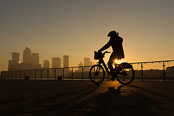 © Licensed to London News Pictures. 20/01/2017. LONDON, UK.  A cyclist travels along the Thames path during hazy sunrise behind the Canary Wharf financial district seen over the River Thames. London is continuing to experience cold weather and has received pollution warnings again this morning. Photo credit: Vickie Flores/LNP