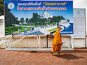 27 AUGUST 2016 - BANGKOK, THAILAND: A Buddhist monk walks past an artist's rendering of the park the city of Bangkok wants to build on what is currently the Pom Mahakan slum community. The legal notice announcing the eviction of the slum's residents is to the right of the picture. The Pom Mahakan community is known for fireworks, fighting cocks and bird cages. Mahakan Fort was built in 1783 during the reign of Siamese King Rama I. It was one of 14 fortresses designed to protect Bangkok from foreign invaders. Only two of the forts are still standing, the others have been torn down. A community developed in the fort when people started building houses and moving into it during the reign of King Rama V (1868-1910). The land was expropriated by Bangkok city government in 1992, but the people living in the fort refused to move. In 2004 courts ruled against the residents and said the city could evict them. The city vowed to start the evictions on Sept 3, 2016, but this week Thai Prime Minister Gen. Prayuth Chan-O-Cha, sided with the residents of the fort and said they should be allowed to stay. Residents are hopeful that the city will accede to the wishes of the Prime Minister and let them stay.       PHOTO BY JACK KURTZ