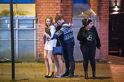 """© Licensed to London News Pictures . 16/12/2017. Manchester, UK. Three people huddle together for warmth as they wait at Deansgate Locks . Revellers out in Manchester City Centre overnight during """" Mad Friday """" , named for historically being one of the busiest nights of the year for the emergency services in the UK . Photo credit: Joel Goodman/LNP"""