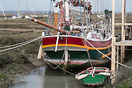 A traditional wooden boat lies in a mud berth in the saltmarsh at Tollesbury, England