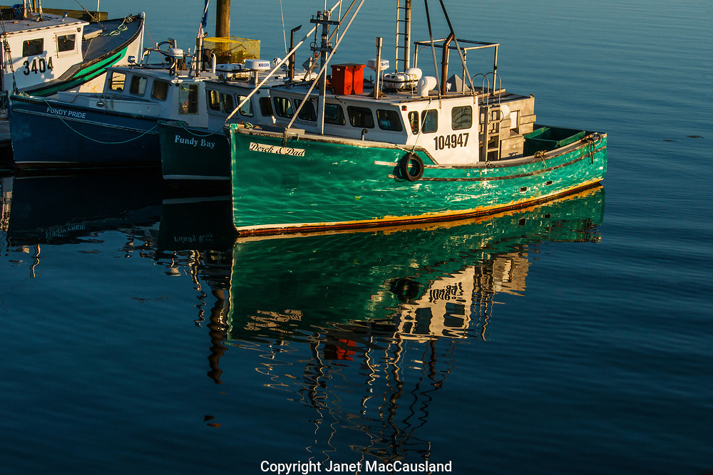 Reflections reflect back onto a green boat's hull in New Brunswick, Canada.