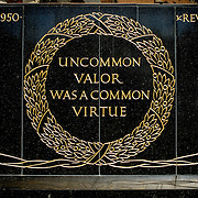 "An inscription of the base of the Iwo Jima Memorial (formally the Marine Corps War Memorial) in Arlington, Virginia, next to Arlington National Cemetery. It reads: ""Uncommon valor was a common virtue,"" a tribute by Admiral Chester Nimitz to the fighting men on Iwo Jima. The monument was designed by Felix de Wledon and is based on an iconic Associated Press photo called the Raising the Flag on Iwo Jima by Joe Rosenthal. It was dedicated in 1954."