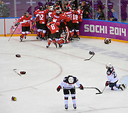 United States' Anne Schleper (L) and Michelle Picard react as Canada celebrates after defeating the United States to win the women's gold medal ice hockey game at the Sochi 2014 Winter Olympics on February 20, 2014 in Sochi, Russia. Canada won 3-2 in overtime. (UPI)