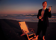 A man in a business suit stands on the beach with a cigar and a smile