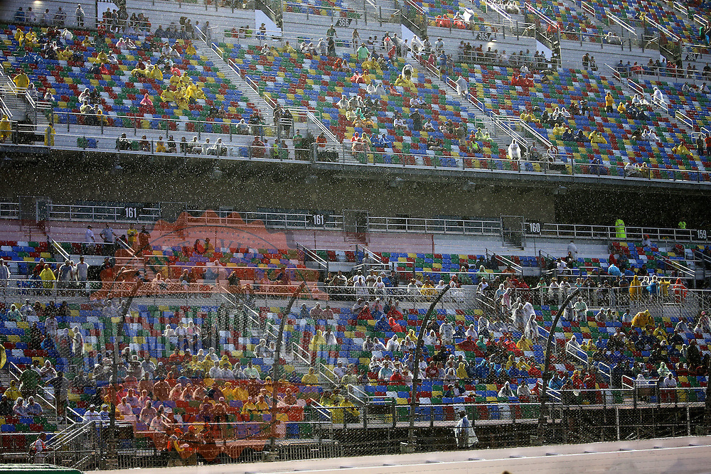 Rain falls as fans watch the driver introductions prior to the 57th Annual NASCAR Coke Zero 400 stock car race at Daytona International Speedway on Sunday, July 5, 2015 in Daytona Beach, Florida.  (AP Photo/Alex Menendez)