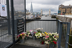 © Licensed to London News Pictures. 18/06/2016. LONDON, UK.  Flowers from friends, family and the local community outside Hermitage Moorings on the River Thames in Wapping, where the MP lived on a houseboat. The Labour MP for Batley and Spen was about to hold her weekly constituency surgery in Birstall Library on16 June 2016 when she was shot and stabbed in the street and later died. Friends and neighbours from the local community continue to visit Hermitage Moorings this morning to pay tribute to Jo Cox.  Photo credit: Vickie Flores/LNP