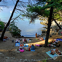Sunbathers in a shaded sheltered cove;<br />Marjan Park, walk and swiming,<br />Split, Croatia. 2018