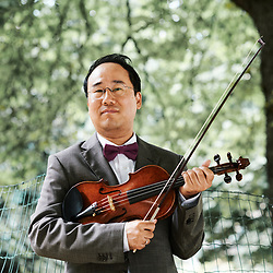 Violinist Hyung Joon Won posing in the Maurice Gardette Square. Paris, France. July 1st, 2019.<br /> Le violoniste Hyung Joon Won prenant la pose au square Maurice Gardette. Paris, France. 1er juillet 2019.
