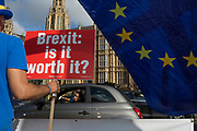 A placard asking passing motorists about the value of a Brexit is attached by pro-Europe anti-Brexit protesters to railings opposite the British Houses of Parliament in Westminster, on 16th October 2018, in London, England.