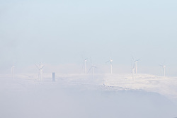 © Licensed to London News Pictures . 23/01/2019. Bolton , UK . Wind turbines emerge from fog on snow-covered hills above Northern Manchester . Clear skies and snow shrouds the hills in the North West as fog descends over Manchester City Centre . Photo credit : Joel Goodman/LNP