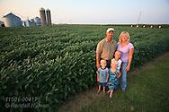 Wellman farm family poses beside soybean field on a summer evening in Lee County, southeast Iowa.