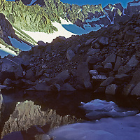 Mount Sill, rising above the Palisade Glacier, reflects in a tarnin the glacier's moraine.  Sierra Nevada, California.