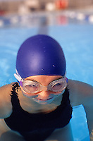young female swimmer in the pool with goggles and cap