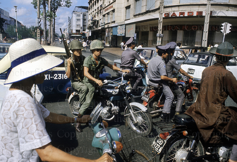 Civilians rush through the streets of Saigon, Vietnam to escape the advance of the North Vietnamese army (NVA) approaching on the outskirts of the capital city. The Vietnam War was fought between 1st November 1955 until the fall of Saigon on 30 April 1975. Photographed  by Terry Fincher. Contact