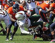 Oct 30, 2010; Charlottesville, VA, USA;   Miami Hurricanes running back Damien Berry (20) is tackled by Virginia Cavaliers linebacker LaRoy Reynolds (9) in the 1st half of the game at Scott Stadium.  Mandatory Credit: Andrew Shurtleff