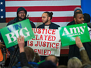 01 MARCH 2020 - ST. LOUIS PARK, MINNESOTA: Supporters of US Sen. Amy Klobuchar try to block the cameras' view of Black Lives Protesters who disrupted a Klobuchar campaign rally. Dozens of Black Lives Matter (BLM) protesters disrupted Sen. Amy Klobuchar's last presidential election rally in Minnesota before Super Tuesday. Almost 500 Klobuchar supporters came to hear Sen. Klobuchar, when the BLM protesters marched into the hall and took control of the stage. Klobuchar cancelled the event about an hour after the BLM protesters entered the hall. The protesters targeted Klobuchar because while she was the Hennepin County Attorney, she oversaw the conviction of Myon Burrell, a black teenager accused and convicted of murder. Evidence has come to light since his conviction that suggests he was wrongly convicted. His conviction has become a flashpoint in Minnesota politics.          PHOTO BY JACK KURTZ