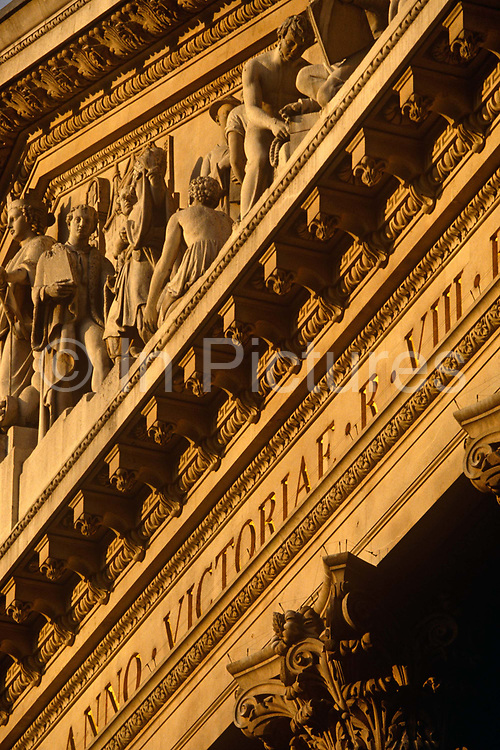 We are looking up from below at the classic neo-Romanesque architecture of the Royal Exchange building in the City Of London, the financial district, otherwise known as the Square Mile. At the top of Doric and Ionic columns with their ornate stonework, powerfully strong lintels cross, bearing the load of fine artistry and carvings which feature the design by Sir William Tite in 1842-1844 and opened in 1844 by Queen Victoria whose name is written in Latin (Victoriae R). It's the third building of the kind erected on the same site. The first Exchange erected in 1564-70 by sir Thomas Gresham but was destroyed in the great fire of 1666. It's successor, by Jarman, was also burned down in 1838. The present building is grade 1 listed and cost about £150,000.