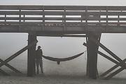 A man arranges his hammock under the Isle of Palms pier in a thick blanket of fog beach near Charleston, South Carolina.