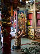 11 JUNE 2015 - MAHACHAI, SAMUT SAKHON, THAILAND: A man prays in the doorway of a Chinese shrine in the fishing port of Mahachai, Thailand. PHOTO BY JACK KURTZ