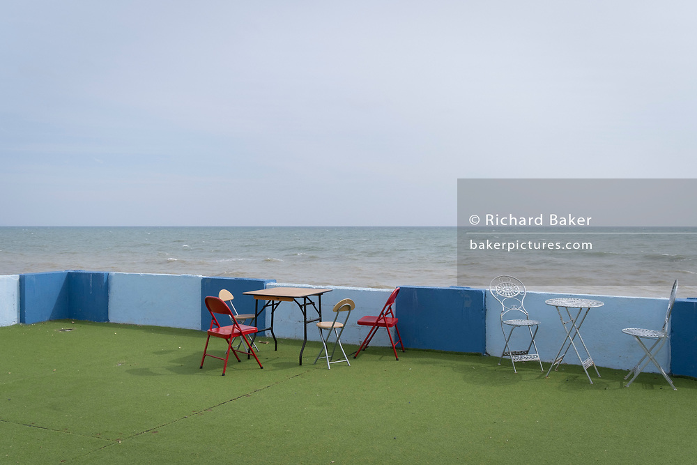 A landscape of chairs and tables against a wall of an outdoor seafront cafe that was once a part of the St Leonards Bathing pool (opened 1933), on 3rd May 2021, in St Leonards, Sussex, England.