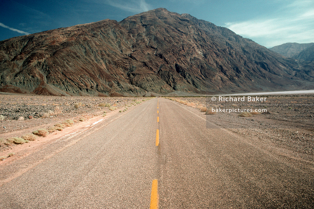 An arid desert landscape of road distance and a mountain geology in Death Valley, on 18th May 1996, in Death Valley, California USA. Death Valley is a desert valley located in Eastern California, in the northern Mojave Desert bordering the Great Basin Desert. It is one of the hottest places in the world at the height of summertime along with deserts in the Middle East. Death Valley's Badwater Basin is the point of the lowest elevation in North America, at 282 feet (86 m) below sea level.( Photo by Richard Baker / In Pictures via Getty Images)