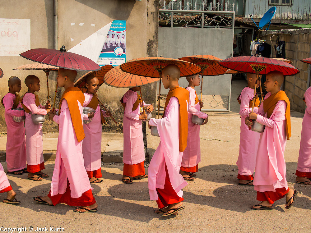 """26 APRIL 2014 - TACHILEIK, SHAN STATE, MYANMAR: Buddhist  nuns go out on their alms rounds in the morning in Tachileik, Shan State, Myanmar (Burma). There are about 75,000 Burmese women living as nuns, sometimes called """"Bhikkhuni"""" although the term has fallen out of favor since Bhikkhuni are no longer ordained. Many of the women who become nuns do so to escape poverty or abuse.   PHOTO BY JACK KURTZ"""