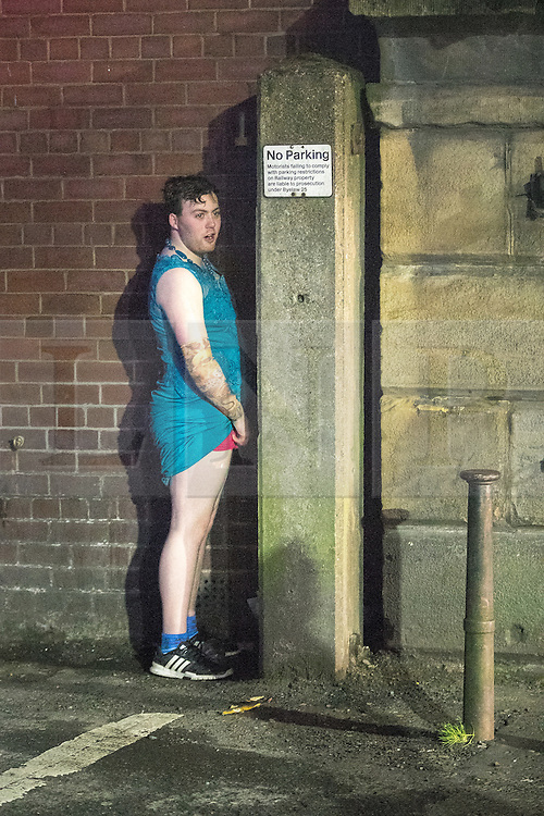 © Licensed to London News Pictures . 27/12/2016 . Wigan , UK . A man in a dress urinates against a wall . Revellers in Wigan enjoy Boxing Day drinks and clubbing in Wigan Wallgate . In recent years a tradition has been established in which people go out wearing fancy-dress costumes on Boxing Day night . Photo credit : Joel Goodman/LNP