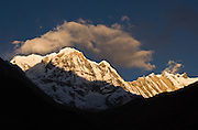 """Sunrise on the east face of Annapurna South (23,684 feet /  7219 meters), in Nepal.  Annapurna South (also known as Annapurna Dakshin, or Moditse) was first climbed in 1964 by a Japanese expedition, via the North Ridge. Annapurna is Sanskrit for """"Goddess of the Harvests."""" In Hinduism, Annapurna is a goddess of fertility and agriculture and an avatar of Durga. On the far right, further away, is Fang (or Baraha Shikhar 25,088 feet / 7647 meters)."""