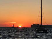 Sunset on the water with catamaran, Oia, Santorini, Greece.
