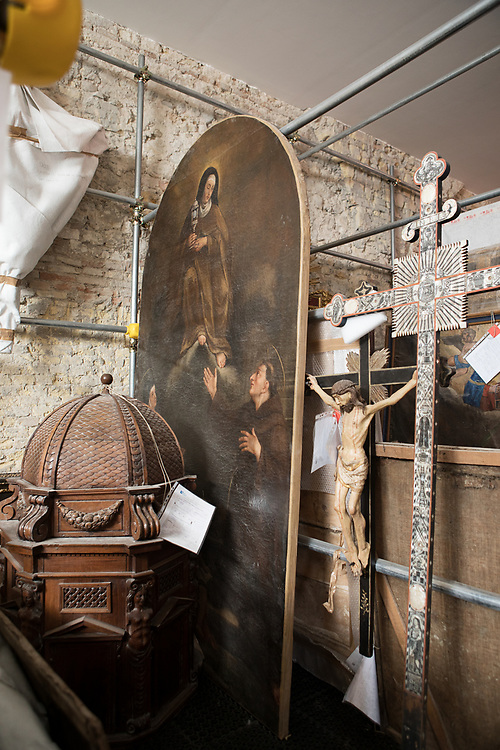 Ancona, Italy, September 21, 2017. Mole Vanvitelliana. The Mole houses artworks saved from the areas affected by the Marche earthquake ofAugust 24, 2016. On the left: the template of the Baptistery of Caldarola (Macerata), and a crucifix from the Monastery of Santa Chiara di Camerino (Macerata). Dusting and disinfection of recovered works is necessary in order to eliminate biological attacks which would otherwise destroy the art object. With wooden objects and paintings on canvas, organic materials extremelu susceptible to biological degradation. All the operations carried out at this stage allow for a brief halting, if necessary, to ensure the proper preservation of the art.