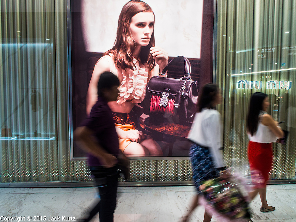 """27 MARCH 2015 - BANGKOK, THAILAND: Shoppers walk past Miu Miu, a high end women's fashions and accessory store in the """"EmQuartier,"""" a new mall in Bangkok. """"EmQuartier"""" is across Sukhumvit Rd from Emporium. Both malls have the same corporate owner, The Mall Group, which reportedly spent 20Billion Thai Baht (about $600 million US) on the new mall and renovating the existing Emporium. EmQuartier and Emporium have about 450,000 square meters of retail, several hotels, numerous restaurants, movie theaters and the largest man made waterfall in Southeast Asia. EmQuartier celebrated its grand opening Friday, March 27.    PHOTO BY JACK KURTZ"""