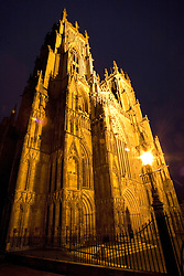 """York, England:  Angled night view of York Minster, the ornate, medieval heart of one of the most historic cities in England's north country..(From """"Layers of History"""" by Dr. Deborah Vess:   Like all medieval cathedrals, the minster stands in the heart of York. Unlike many medieval cathedrals, it is not built on elevated ground. The Minster, like York, contains many layers of history. Although the origins of the Minster can be traced back to the first Christian period in York's history, the reign of Edwin of Northumbria, the present structure dates from the rebuilding project of Archbishop Roger Pont l'Eveque, who, starting in 1154, built the choir, and Archbishop Walter de Grey, who began the south transept in 1220. the nave dates from 1291. The rebuilding project continued for over two centuries, and as not complete until 1472. The York Minster contains more medieval glass than any other Cathedral in Europe.   The City of York, England, is a living testament to the continuity between the historic past and the present. A walk through York is a journey through England's Roman, medieval, and Viking heritage. York is still surrounded by its medieval walls, and in places one can still see the Roman foundations upon which these walls were built."""