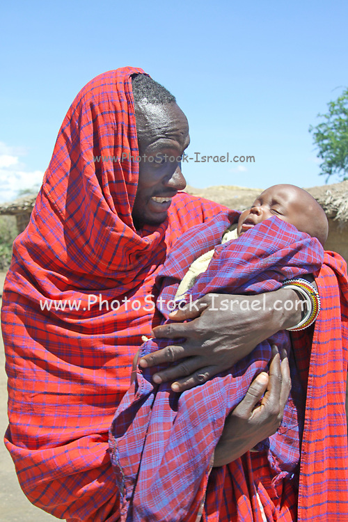Africa, Tanzania, close up portrait of a male member of the Datooga tribe holding his baby