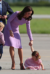 Princess Charlotte is helped up by the Duchess of Cambridge after she fell over during their visit to Airbus in Hamburg, Germany.