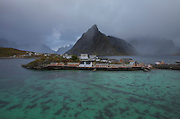 Approaching rain showers over Sakrisøy and Olstind mountain peak, Moskenesøy, Lofoten Islands, Norway