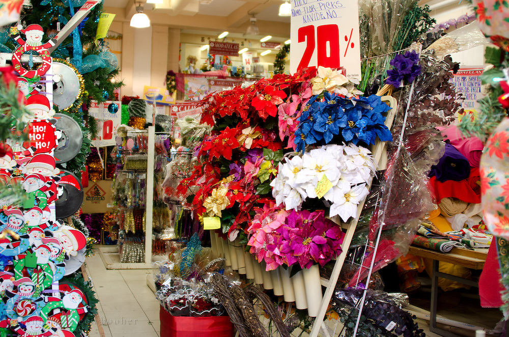 Store having sale on Christmas decorations, including blue, purple, and red faux poinsettias, Oaxaca. Mexico.
