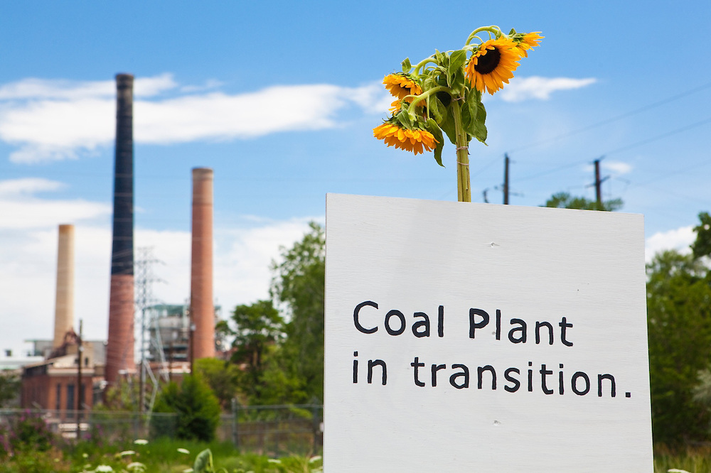 """The sign """"coal Plant in transition"""" and sunflowers placed in front of the coal-fired Valmont Power Plant in Boulder, Colorado to protest its continued operation."""