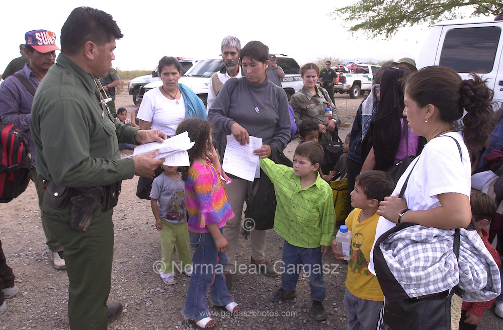 U. S. Border Patrol agents process some of the illegal immigrants stopped by agents on Route 19 on the Tohono O'odham Reservation.  A group of seven vehicles stuffed with entrants attempted to outrun agents after cutting and driving through the border fence near the San Miguel gate at the Mexican border.  Agents stopped three of the vehilces.  Four managed to escape apprehension.  (PHOTO: NORMA JEAN GARGASZ)