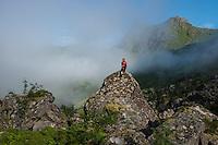 Female hiker sits on rock in isolated mountain valley near Unstad, Vestvågøy, Lofoten Islands, Norway