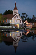 Small white clapboard church reflected in flooded waters