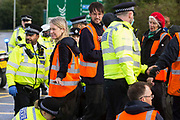 Metropolitan Police officers monitor Insulate Britain climate activists who had previously blocked a M25 slip road at Junction 14 close to Heathrow airport and then glued themselves together as part of a campaign intended to push the UK government to make significant legislative change to start lowering emissions on 27th September 2021 in Colnbrook, United Kingdom. The activists are demanding that the government immediately promises both to fully fund and ensure the insulation of all social housing in Britain by 2025 and to produce within four months a legally binding national plan to fully fund and ensure the full low-energy and low-carbon whole-house retrofit, with no externalised costs, of all homes in Britain by 2030.