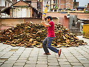 01 AUGUST 2015 - KATHMANDU, NEPAL: Boys practice cricket batting in front of a pile of bricks recovered for earthquake reconstruction. The Nepal Earthquake on April 25, 2015, (also known as the Gorkha earthquake) killed more than 9,000 people and injured more than 23,000. It had a magnitude of 7.8. The epicenter was east of the district of Lamjung, and its hypocenter was at a depth of approximately 15 km (9.3 mi). It was the worst natural disaster to strike Nepal since the 1934 Nepal–Bihar earthquake. The earthquake triggered an avalanche on Mount Everest, killing at least 19. The earthquake also set off an avalanche in the Langtang valley, where 250 people were reported missing. Hundreds of thousands of people were made homeless with entire villages flattened across many districts of the country. Centuries-old buildings were destroyed at UNESCO World Heritage sites in the Kathmandu Valley, including some at the Kathmandu Durbar Square, the Patan Durbar Squar, the Bhaktapur Durbar Square, the Changu Narayan Temple and the Swayambhunath Stupa. Geophysicists and other experts had warned for decades that Nepal was vulnerable to a deadly earthquake, particularly because of its geology, urbanization, and architecture.          PHOTO BY JACK KURTZ