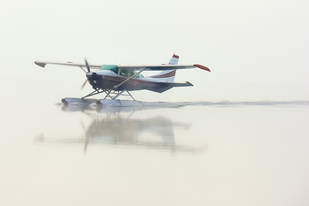 A Cessna 206 emerges through the fog as it sets up for take off on Schwatka Lake, Yukon