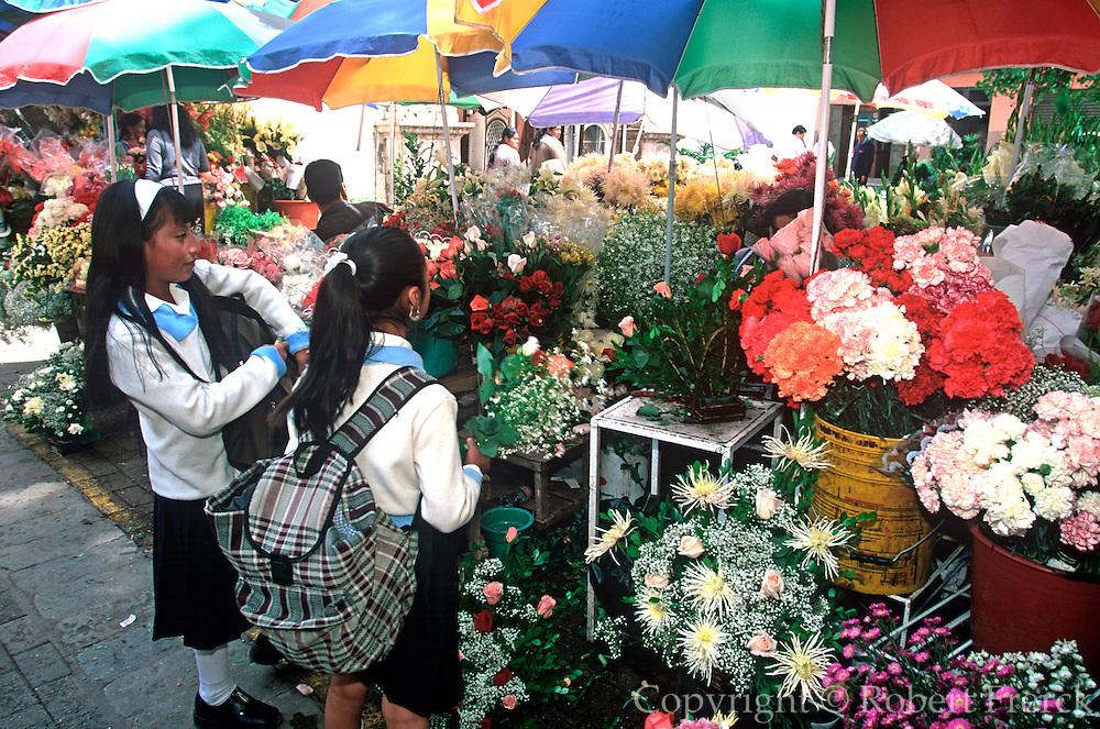 ECUADOR, HIGHLANDS, CUENCA school children in flower market