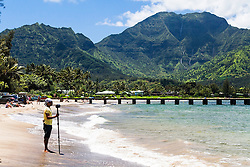 """Hanalei Bay, is the largest bay on Kauai. Hanalei means """"crescent bay"""" in Hawaiian. It is a long half moon of golden sand backed by 4,000-foot-high green mountains. Look closely and you may be able to spot several waterfalls."""