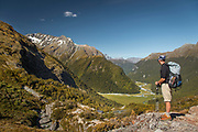 Side view of a male hiker with a backpack looking at the view of a valley, Routeburn Track, South Island, New Zealand