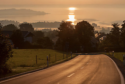 Road leading to village at lakeside, Hittenkirchen, Lake Chiemsee, Bavaria, Germany