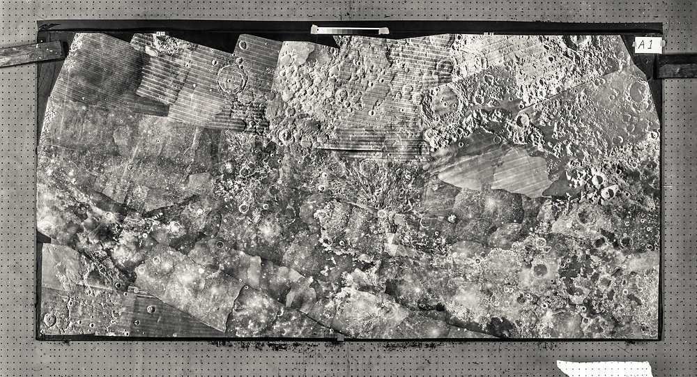 Photographic print; mosaic of lunar images from various sources including orbiters, arranged on copy board.  For production of maps of lunar surface and navigation charts used during Moon landings. ACIC in St. Louis, Mo.