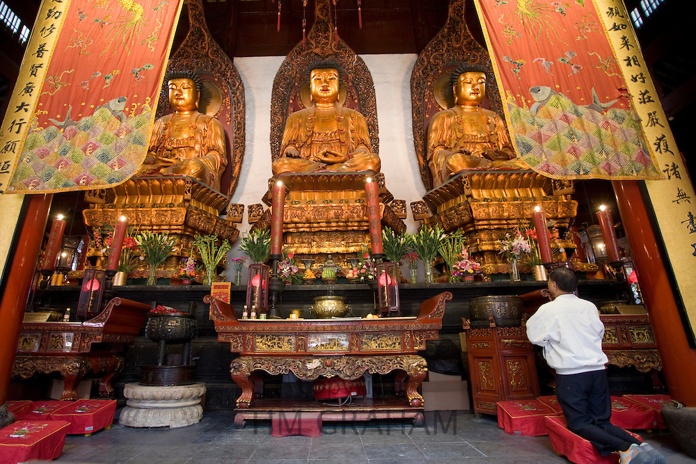 Man prays to Golden Buddhas in the Grand Hall of Magnificence of the Jade Buddha Temple, Shanghai, China
